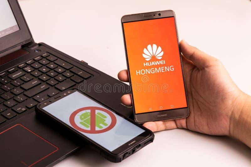 Osoba trzyma Huawei dzwoni bez Android signage i inny z Hongmeng OS obrazkiem, U S firmy zaczynali ograniczać sprzedaże t zdjęcia stock