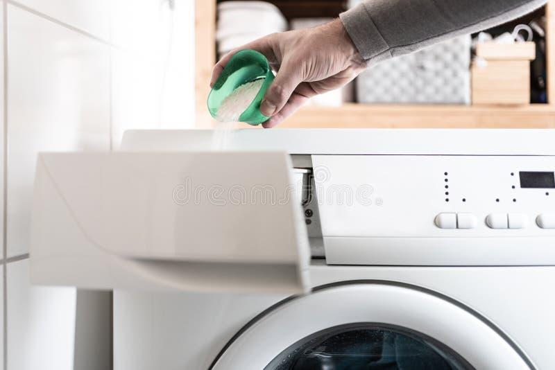 Osoba używa dawkowanie pomoc pout pralnianego detergentu proszek w pralkę obrazy royalty free