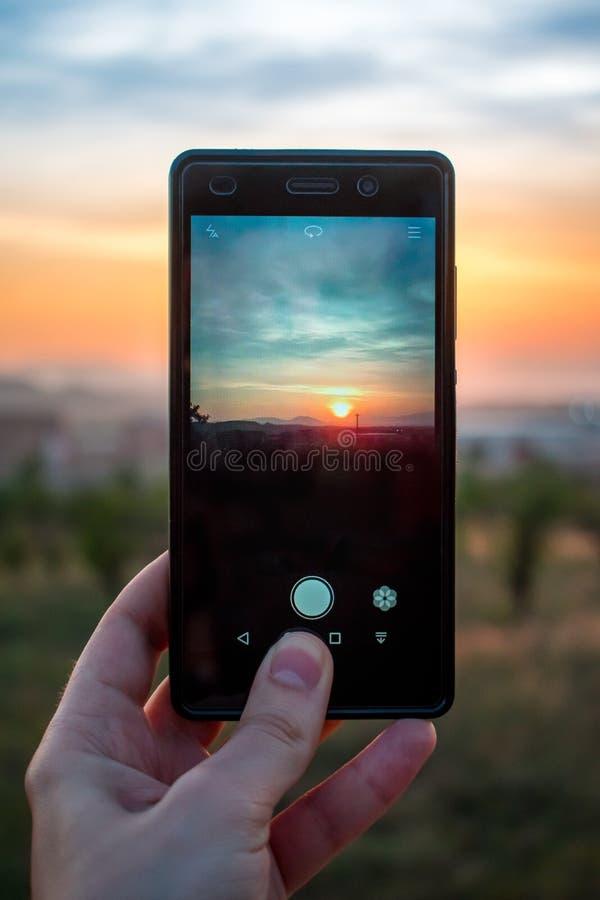 Osoba używa telefon komórkowego bierze fotografię zmierzch fotografia stock
