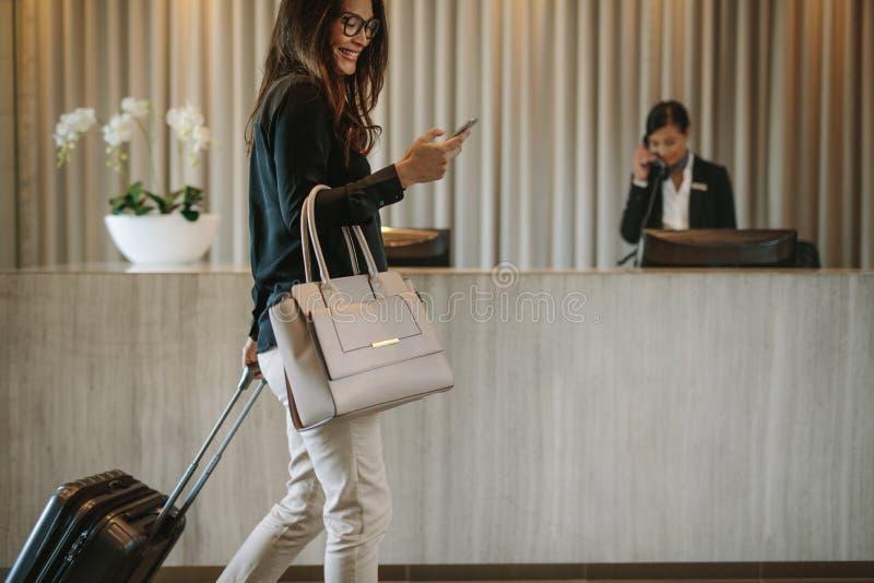 Osoba w podróży służbowej w hotelowym korytarzu z telefonem obraz royalty free