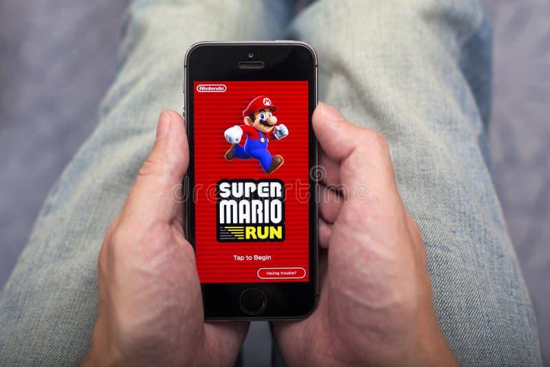 Osoba wręcza mienia iPhone z Super Mario bieg grze app obrazy stock