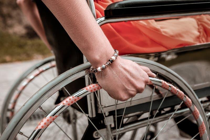 Osoba z inwalidzkim obsiadaniem w kładzenie ręce na kole i wózku inwalidzkim fotografia royalty free