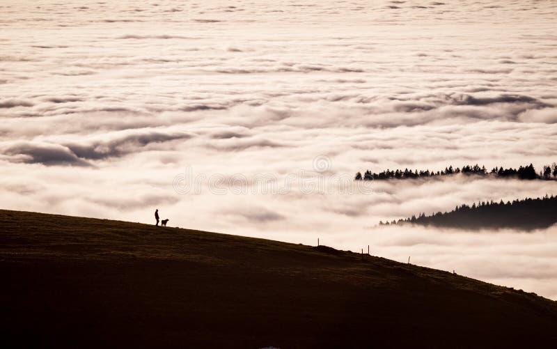 Osoba z psem w krajobrazie nad mgła zdjęcie royalty free