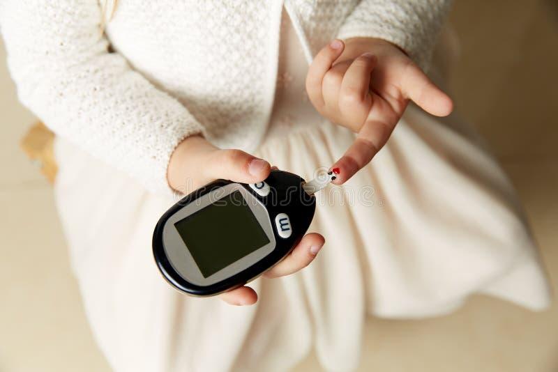 Osoba zależna pierwszy typ cukrzycy glikozy pozioma cierpliwy pomiarowy badanie krwi używać ultra mini glucometer i małą kroplę zdjęcia stock