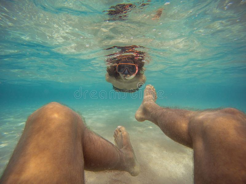 Osobista perspektywa m?ski dop?yni?cie backwards podwodny M?oda kobieta pod??a jej ch?opaka fotografia royalty free