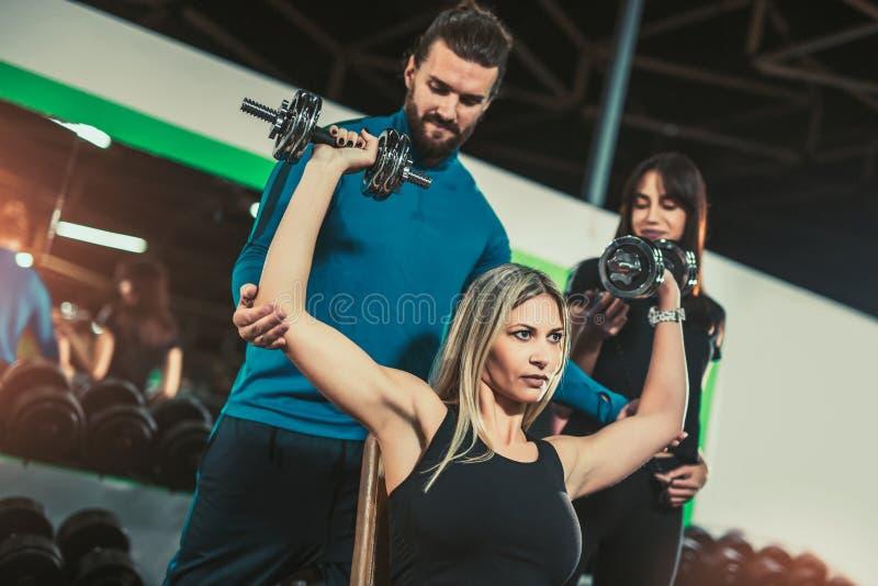 Osobistego trenera pomaga kobieta pracuje z dumbbells obraz stock