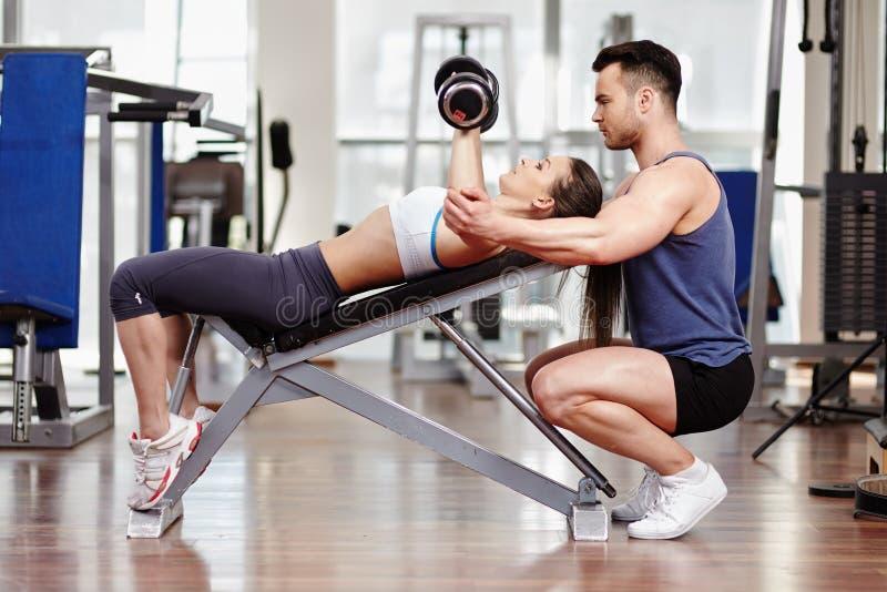 Osobistego trenera pomaga kobieta przy gym zdjęcia royalty free