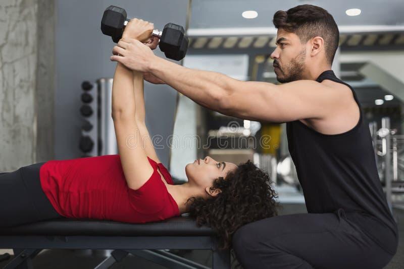 Osobistego trenera pomaga kobieta z exersices w gym zdjęcie stock