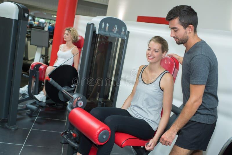 Osobistego trenera pomaga kobiety pracujące w gym out obraz stock