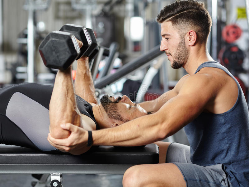 Osobisty instruktor pomaga mężczyzna w gym zdjęcia stock