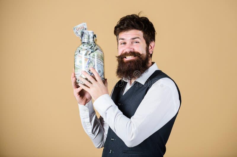 Osobisty ksi?gowy Biznesmen z jego dolarowymi oszcz?dzaniami Bogactwo i wellbeing Obsługuje brodatego faceta chwyta słój gotówka  obraz stock