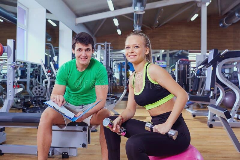 Osobisty trener i kobieta relaksuje w gym po ćwiczenia fotografia stock