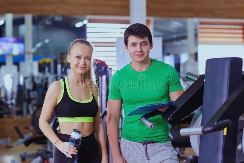 Osobisty trener i kobieta relaksuje w gym po ćwiczenia obrazy stock