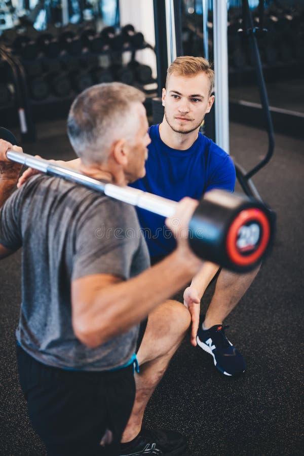 Osobisty trener i starszy mężczyzna ćwiczy przy gym zdjęcia stock