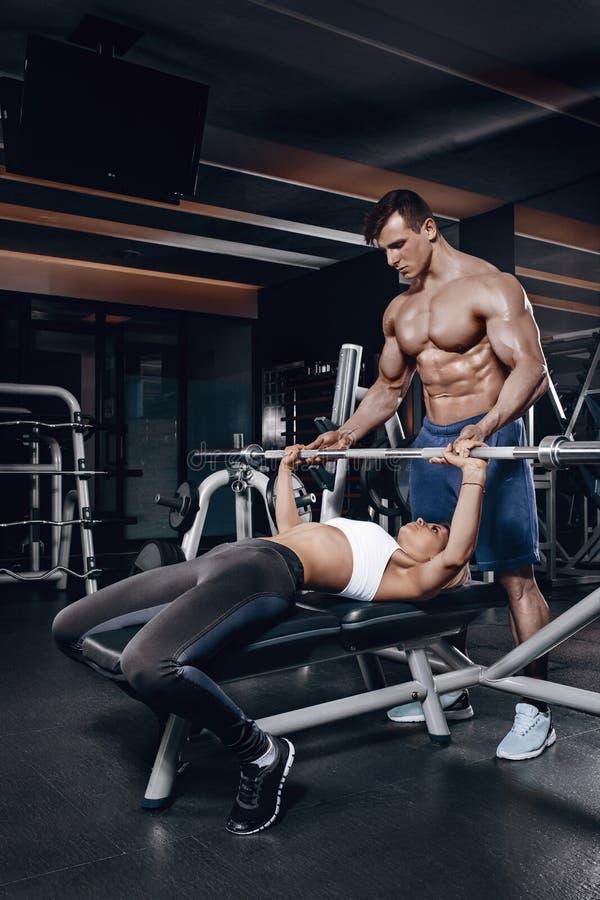 Osobisty trener pomaga młodej kobiety podnosić barbell podczas gdy pracujący w gym out obraz royalty free