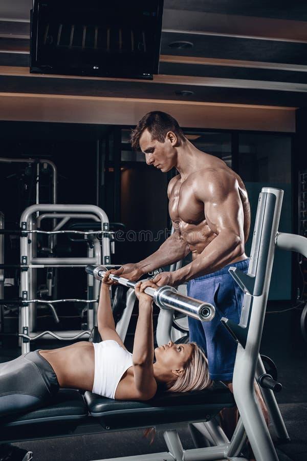 Osobisty trener pomaga młodej kobiety podnosić barbell podczas gdy pracujący w gym out fotografia royalty free