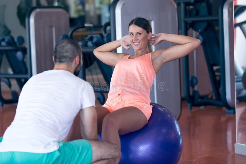 Osobisty trener pracuje z jego klientem w gym obrazy royalty free