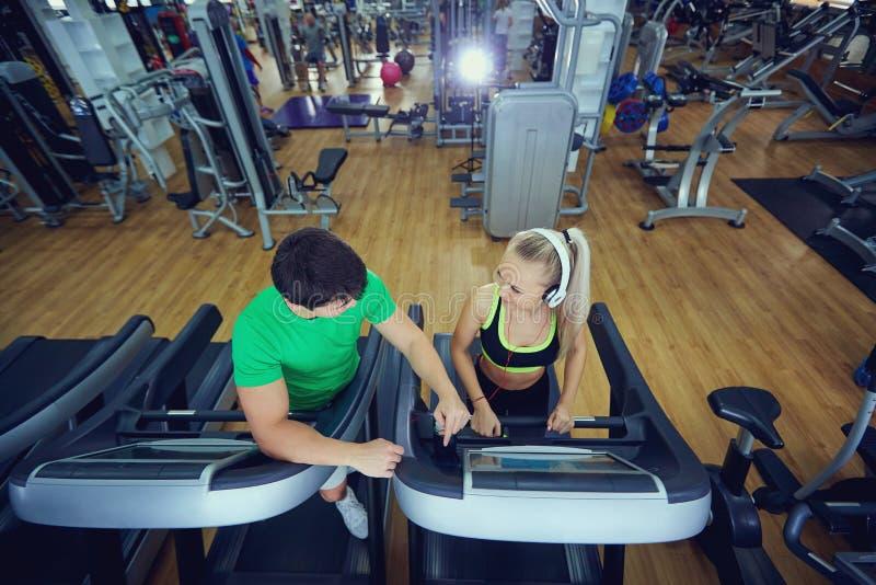 Osobisty trenera mężczyzna z sportową dziewczyną na karuzeli w gy fotografia royalty free