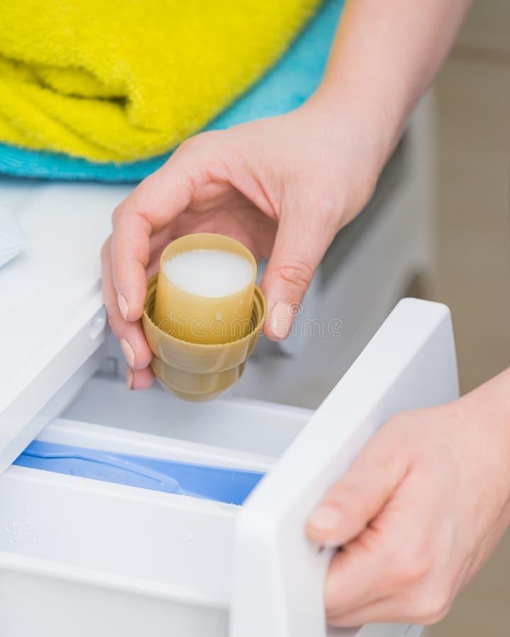 Osoby dolewania tkaniny softener w pralk? zdjęcia stock