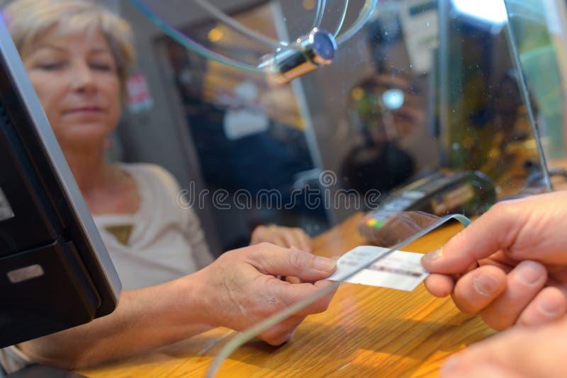 Osoby kupienia filmu bilety od żeńskiego sprzedawcy przy kinem fotografia stock