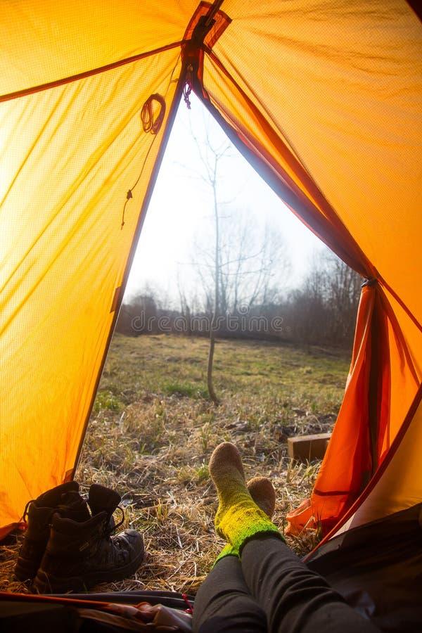 Osoby obsiadanie w pomarańczowym namiocie, obóz w banku rzeka w wiośnie Cieki selfie podróżnik Zrelaksowany, kolorowy spojrzenie, zdjęcie royalty free