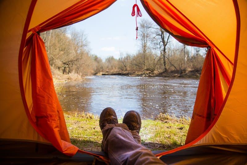 Osoby obsiadanie w pomarańczowym namiocie, obóz w banku rzeka w wiośnie Cieki selfie podróżnik Zrelaksowany, kolorowy spojrzenie, obrazy stock