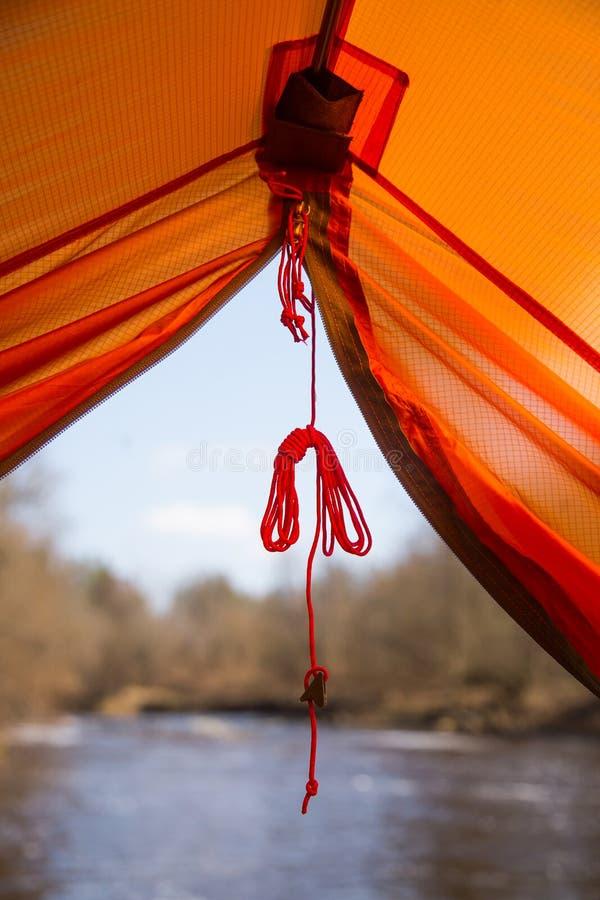 Osoby obsiadanie w pomarańczowym namiocie, obóz w banku rzeka w wiośnie Cieki selfie podróżnik Zrelaksowany, kolorowy spojrzenie, obraz royalty free