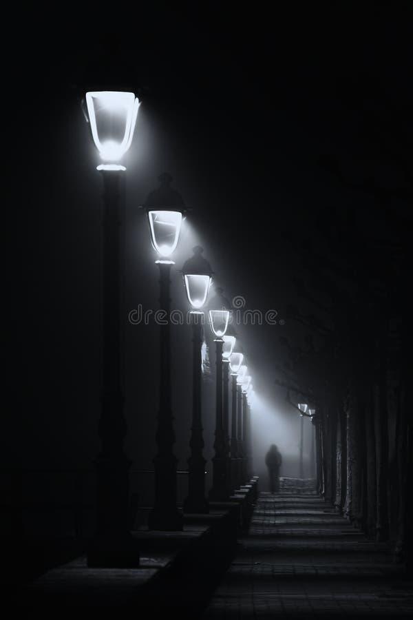 Osoby odprowadzenie na ciemnej ulicie iluminującej z streetlamps fotografia royalty free