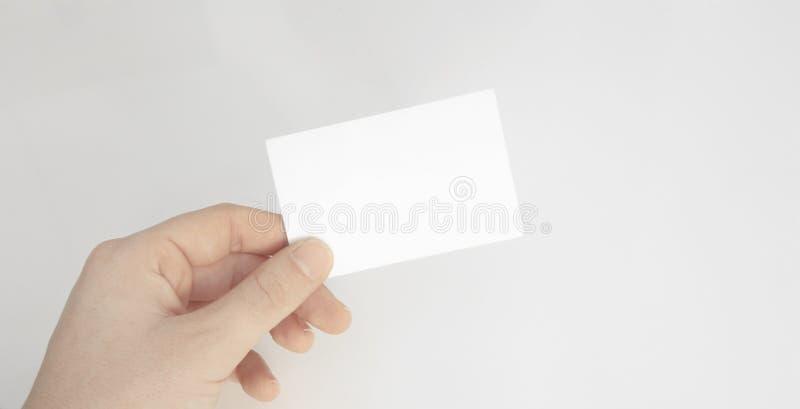 Osoby ręka trzyma pustą papierową kartę odizolowywał biały tło fotografia royalty free