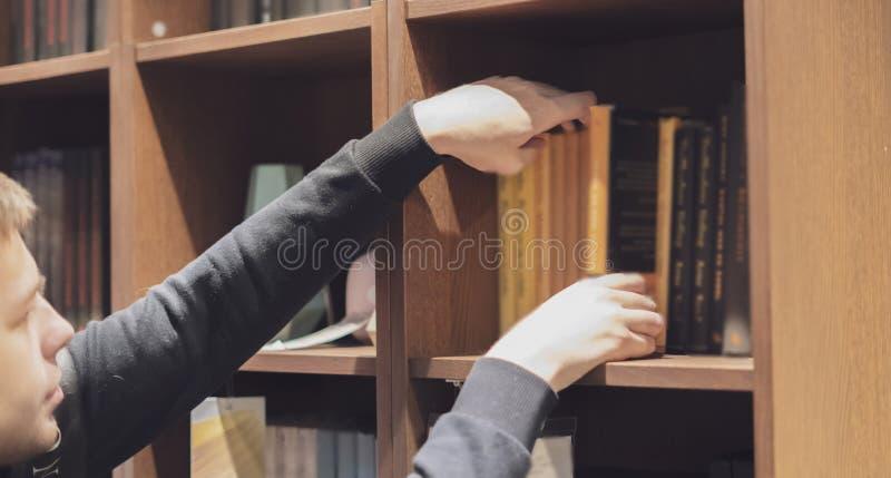 Osoby ręki gmeranie dla książki na książkowej półce n w domu obraz stock