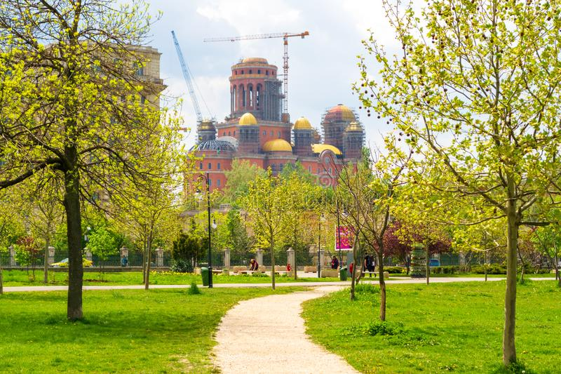 Osoby salwowanie Katedralny Catedrala Mantuirii Neamului widzieć od Izvor parka Parcul Izvor w Bucharest jak, Rumunia zdjęcia stock