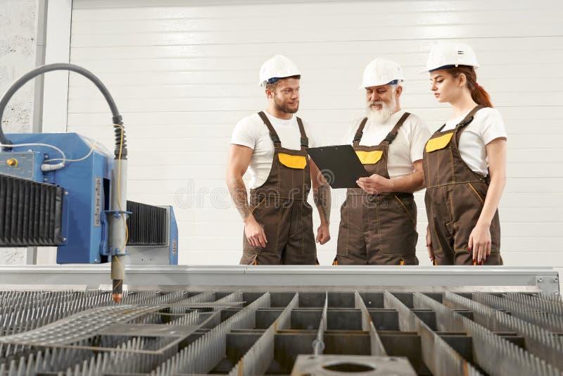 Osocze krajacz i trzy inżyniera opowiada, patrzejący falcówkę zdjęcie stock