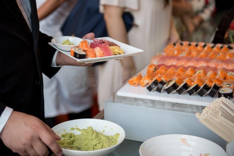 Ospite con la barra del buffet dei sushi, approvvigionamento del buffet dell'alimento fotografie stock
