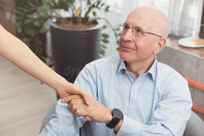 Ospite di salute e un uomo senior durante la visita domestica immagine stock libera da diritti