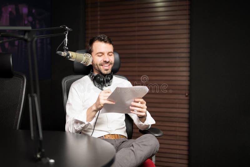 Ospite radiofonico maschio che trasmette per radio una manifestazione in studio fotografia stock