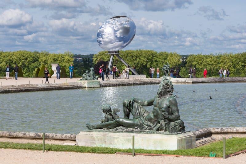 Ospiti nel palazzo Versailles del giardino con la statua ed in stagno a Parigi, Francia immagine stock libera da diritti