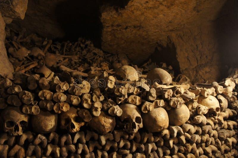 Ossa e crani accatastati nelle catacombe di Parigi immagini stock