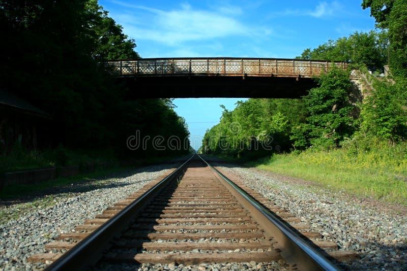 Osservando giù i binari ferroviari con il ponticello immagini stock libere da diritti
