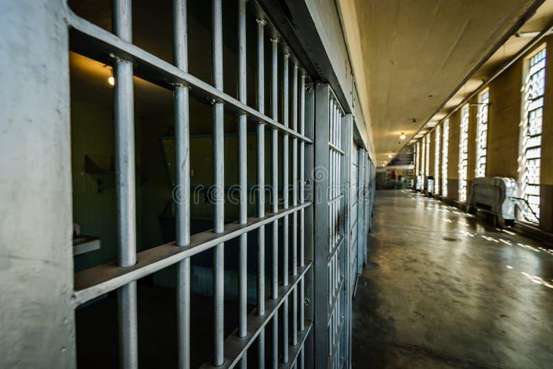 Osservando giù il blocchetto di cella di prigione le barre immagine stock
