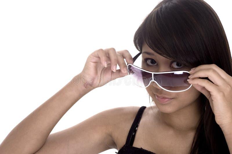 Osservando sopra gli occhiali da sole fotografia stock