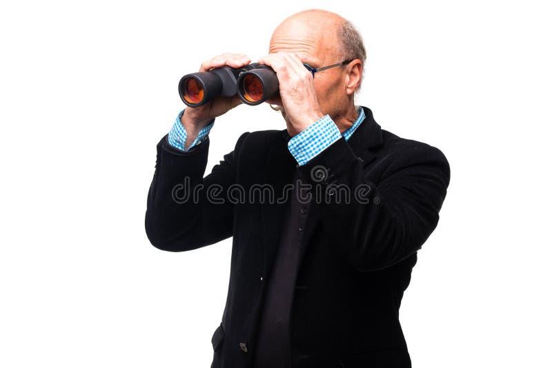 Osservazione bella dell'uomo senior tramite il binocolo su fondo bianco fotografia stock