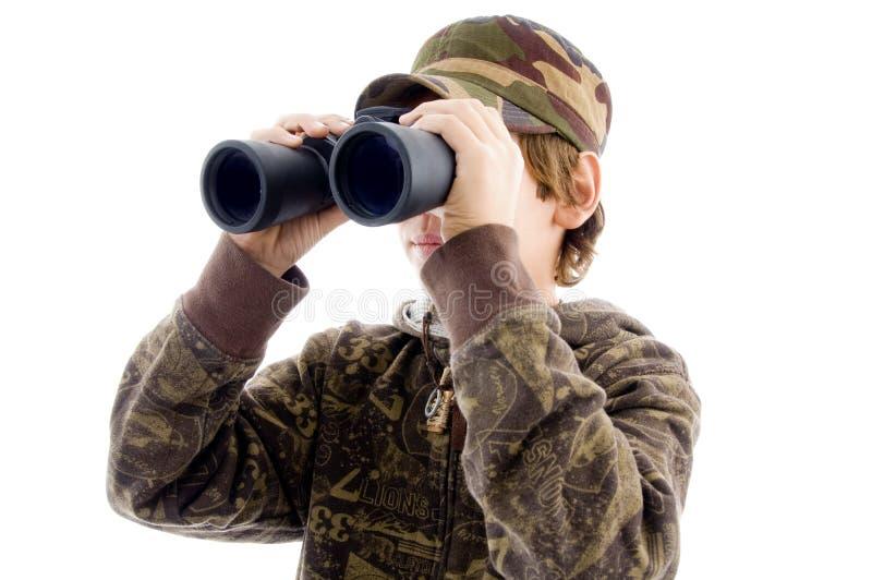 Osservazione del ragazzo di vista frontale tramite il binocolo fotografia stock libera da diritti
