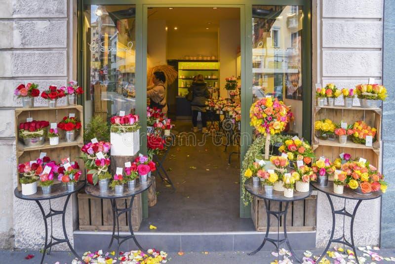 Osservi l'esterno di un negozio mentre gli assistenti sistemano i fiori ad un fiorista dello specialista a Milano, Italia fotografia stock libera da diritti