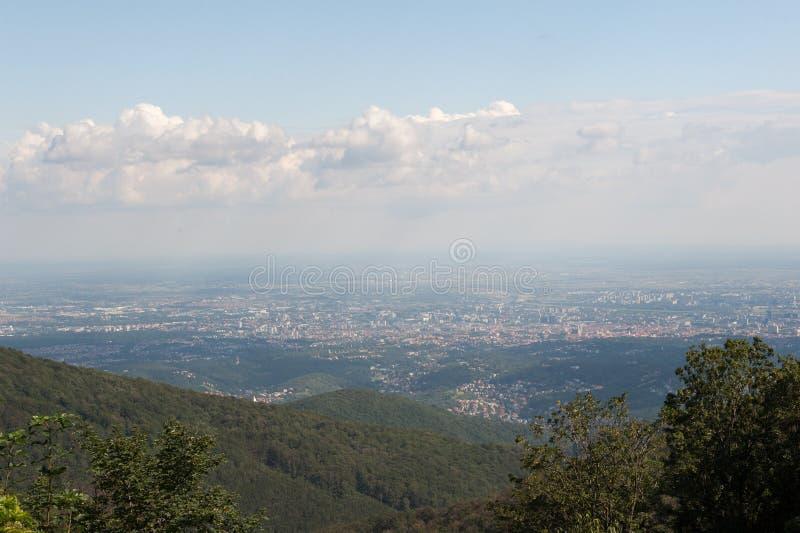 Osservi la capitale Zagabria da Medvednica, montagna del od Croazia di Sljeme con la foresta verde, il cielo blu e le nuvole bian immagine stock