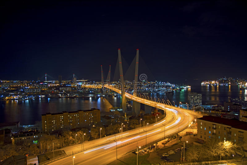 Osservi la città alla notte, il ponte attraverso la baia alla notte, piena delle luci intense immagine stock