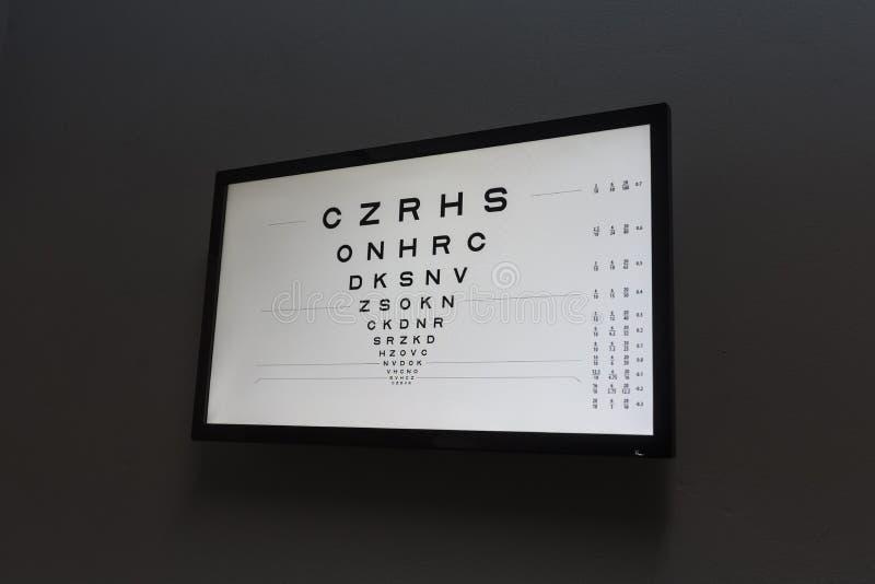 Osservi la prova nella stanza scura dell'optometrista per la visione del cliente di prova con la s immagini stock