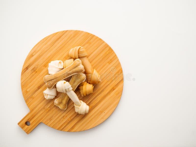 Osso del cibo per cani sullo spezzettamento del legno a pezzi su bianco fotografie stock