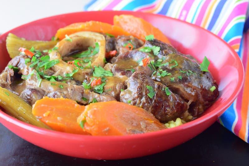 Ossobuco tradizionale italiano con le carote cucinate, patata, cellery del piatto del vitello in una ciotola ceramica rossa fotografia stock libera da diritti