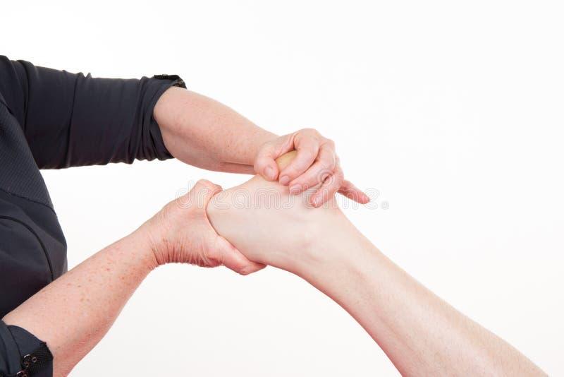 Ostéopathe faisant le massage de réflexothérapie sur le pied masculin sur le fond coloré photographie stock