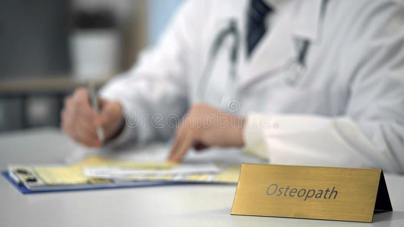 Ostéopathe masculin attentif causant avec le patient sur l'ordinateur portable, système de santé image libre de droits
